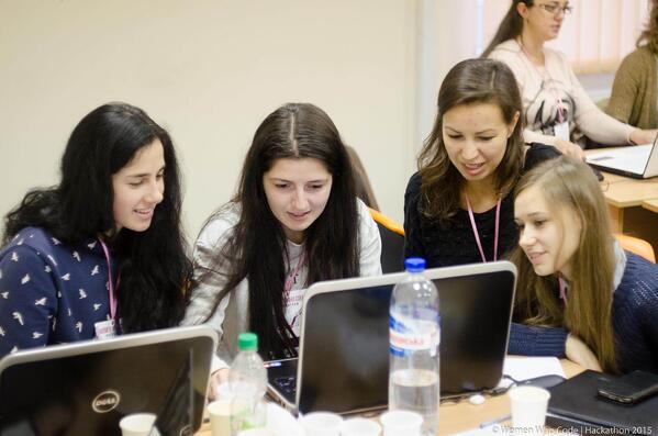 Image of women who code volunteers working together at a laptop